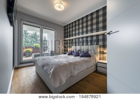 Modern bedroom with checker pattern on the wall and big window
