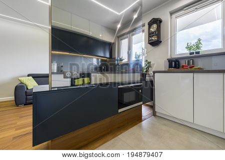 Modern kitchen interior design witch mirror wall in white and black finish