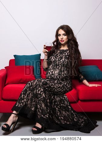 Pregnant woman with red wine glass sitthing on sofa. Dangerous life style and unhealthy behaviour of mother-to-be