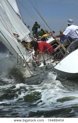 The men work with navigation of a yacht in the difficult storm sea. The present man's sports it yachting!