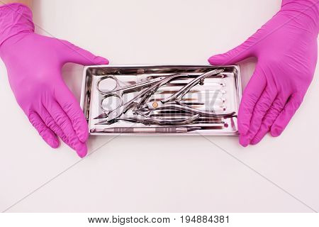 Manicure professional tools closeup on white background. Nailcare instrument in beautician's hands top view with copy space.