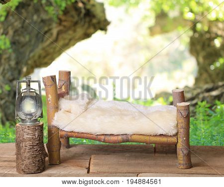 A   bed studio photography prop with a railroad lantern and a wooded forest camping background.  The bed is made from a Coral Bark Japanese Maple tree.