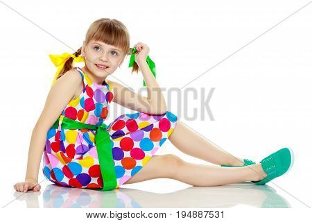 A beautiful Caucasian little blonde girl with long pigtails, in which large colored bows are braided, and a short bangs on her head. In a short summer dress, a pattern of multi-colored circles.