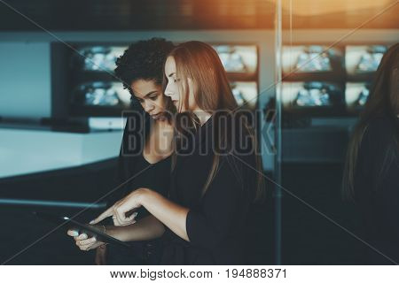 Two young female co-workers looking at something on screen of digital tablet in luxury office young afro american probationer girl consult an beautiful white businesswoman about future presentation