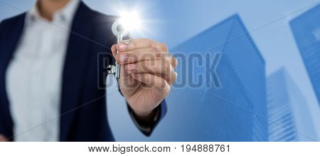 Mid section of businesswoman showing new house key against illuminated buildings in city against sky