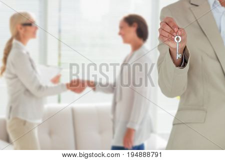 Mid section of female executive showing new house key against woman and therapist shaking hands