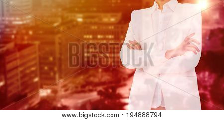 Mid section of businesswoman with arms crossed against illuminated roads by buildings in city