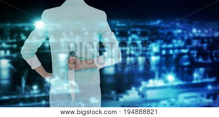 Rear view of businesswoman hiding knife against illuminated harbor against cityscape