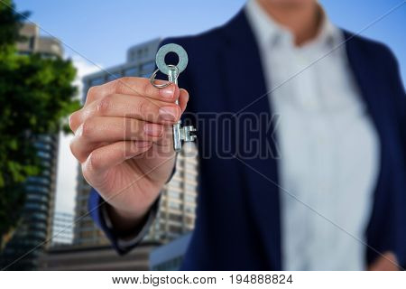 Mid section of businesswoman showing new house key against beautiful cityscape against clear sky