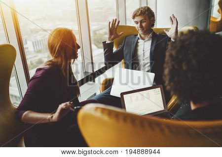 Young businessman with laptop is angry annoyed impatient and giving up during his meeting with two businesswomen on yellow armchairs near big window of office skyscraper with cityscape outside