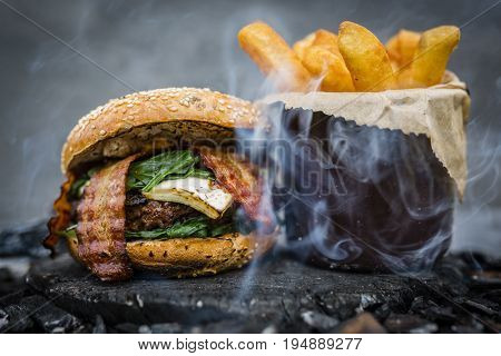 Tasty smoked grilled and glazed beef burger with lettuce, cheese and bacon served with french fries on wooden table with copyspace, smoke mesquite timber wood in background.