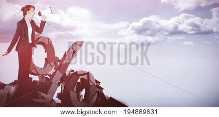 Businesswoman with loudspeaker against blue sky