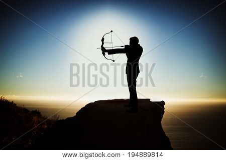 Silhouette businessman taking aim with bow and arrow  against scenic view of mountain by sea against sky