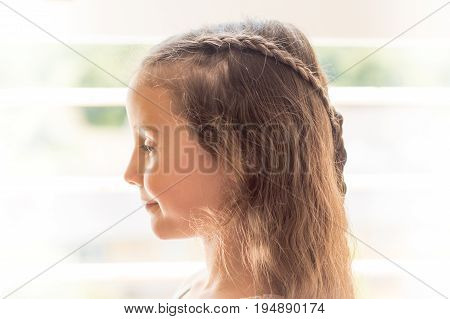 High-key portrait of girl with braided hair. Child with long brown with hairstyle with plaits in front of window