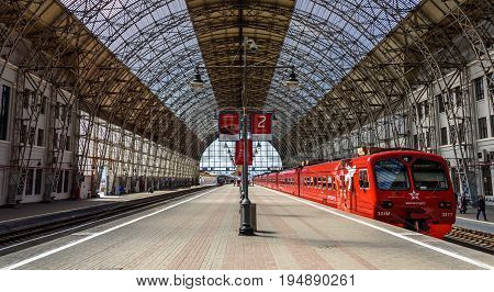 MOSCOW, RUSSIA - MAY 05, 2017: Red Aeroexpress train standing at a gigantic landing platform of Moscow Kiyevskaya railway station and Shukhov's steel-and-glass roof of Kiyevsky station