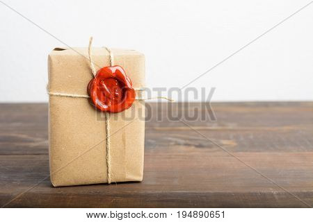 Parcel Wrapped In Craft Paper With Rope And Red Sealing Wax Over The Wooden Table