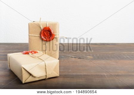 Two Gifts Wrapped In Craft Paper With Rope And Red Sealing Wax Over Brown Wooden Table