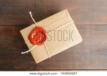 Parcel Wrapped In Craft Paper With Rope And Red Sealing Wax Over Brown Wooden Table