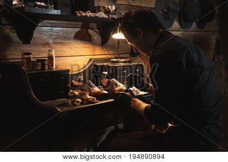 Image of young handsome man shoemaker at footwear workshop.