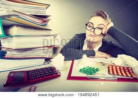 Health concept at business work. Tired overworked young businesswoman secretary manager. Sick ill young female sleeping at workplace.