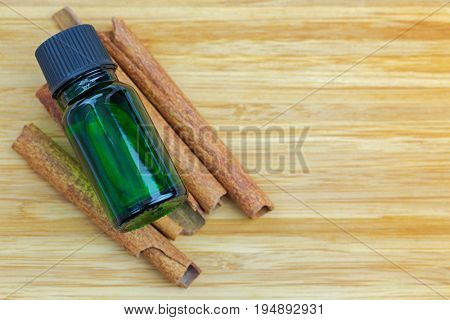 Pure Cinnamon essential concentrate oil extract in green bottle on Cinnamon sticks on wooden background with copyspace
