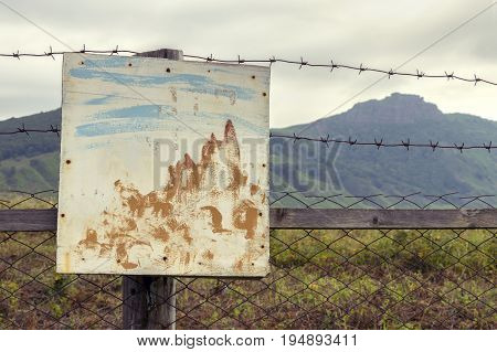 Painted sign on the fence of barbed wire and a grass field on the background of the mountains.