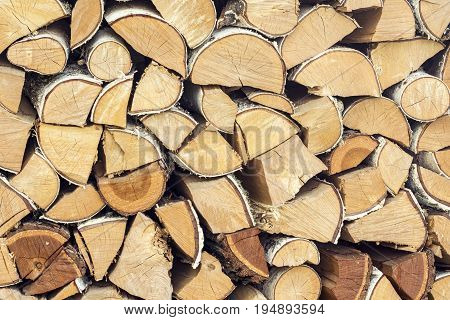 Natural wooden background closeup of chopped firewood logs. Chopped firewood on a stack
