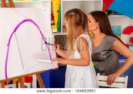 Children painting brush on easel first time . Kids girl and boy with teacher learn paint in class school. Child picture on background. Small student draw rainbow. Back to school.