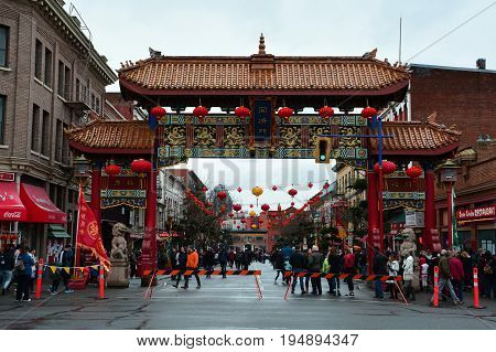 Victoria BC,Canada,January 27th 2017.The gates of Harmonius Interest guard Canada's oldest Chinatown in Victoria BC.People enjoying Chinese New Year in Victoria's Chinatown.