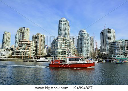 Vancouver BC,Canada,February 20th 2017.A fire rescue boat goes by the waterfront condos at False Creek a part of Vancouver's vast skyline.Come to Vancouver and enjoy your experience.