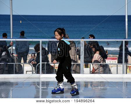 Sydney Australia - Jul 9 2017. Little asian girl ice skating on Bondi ice rink. Australia's only beachside ice rink is on Bondi beach during Winter Festival.