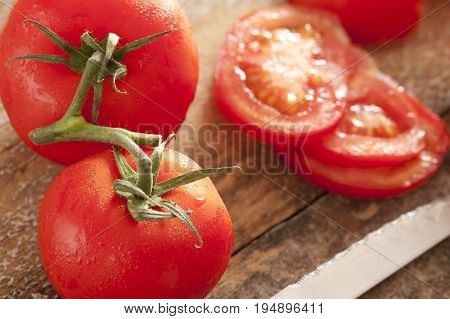 Fresh washed tomatoes with droplets of water on the vine and sliced ready for inclusion in a healthy summer salad on a wooden board with knife