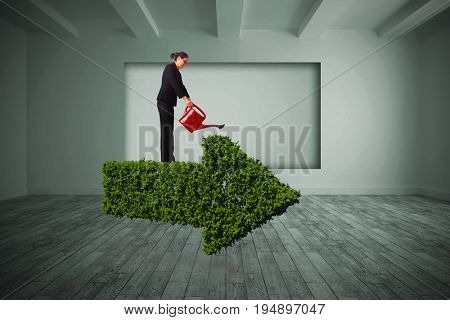 Businesswoman using red watering can against white room with screen in wall