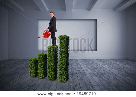 Businessman holding red watering can against white room with screen in wall