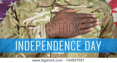 Mid section of soldier taking oath against waving flag of america