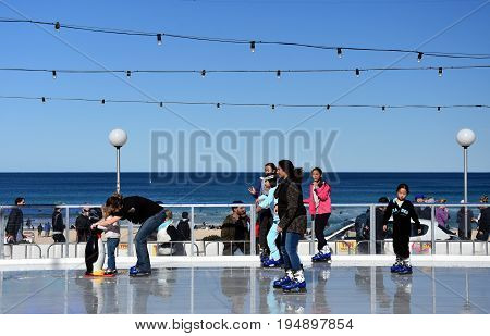 Sydney Australia - Jul 9 2017. Kids and parents ice skating with a Penguin Skate Aid on Bondi ice rink. Australia's only beachside ice rink is on Bondi beach during Winter Festival.