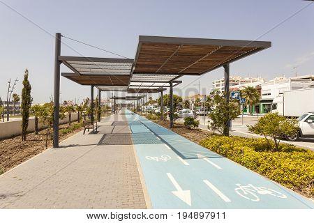 San Pedro de Alcantara Spain - June 1 2017: Blue bicycle lane in the city of San Pedro de Alcantara. Malaga Province Andalusia Spain