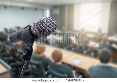 Microphone over the blurred business conference hall or seminar room Blurred background