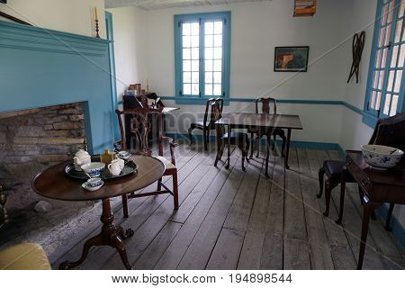 MACKINAW CITY, MICHIGAN / UNITED STATES - JUNE 18, 2017: Colonial era furniture and housewares are displayed in a house at Fort Michilimackinac, in the Colonial Michilimackinac State Park.