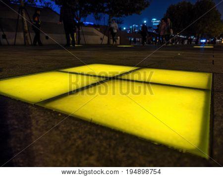 Shanghai, China - Nov 4, 2016: Night footpath lights along The Bund on Zhongshan East 1st Road. Pedestrians walking along to enjoy night view. Low-light image.