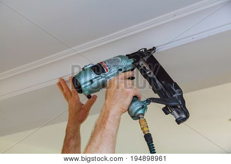 Carpenter brad using nail gun to Crown Moulding framing trim, with the warning label that all power tools have on them shown illustrating safety concept