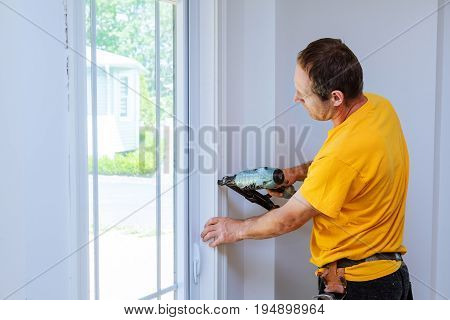 Carpenter using nail gun to moldings on windows, framing trim, with the warning that all power tools have on them shown illustrating safety concept