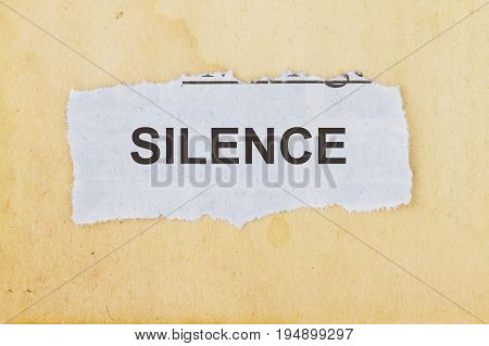 Silence newspaper cutout in an old paper background.