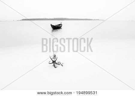 High key image of a boat on water tied by a rope with an anchor on river bed. Tajpur West Bengal India. Minimalistic image with black and white.