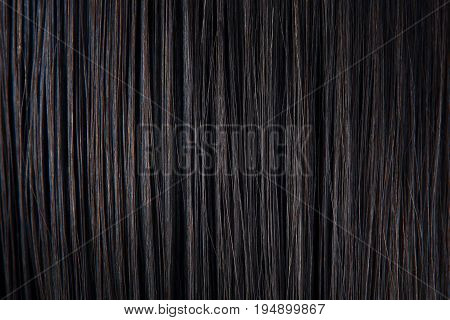 Straight black hair close-up. Texture of dark woman hair. Black female hair background.
