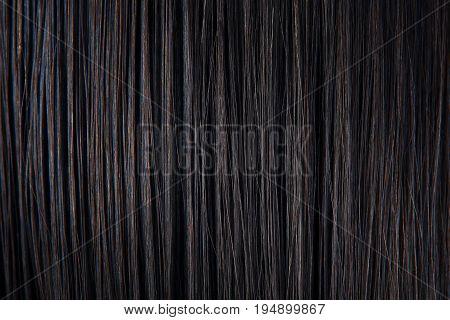Straight black hair close-up. Texture of dark woman hair. Black female hair background.