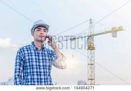 Portrait of architect wear white helmet safty talking on smartphone at construction site with crane background