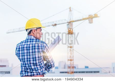 Portrait of architect wear yellow helmet safty hold the blueprint on construction site with crane background