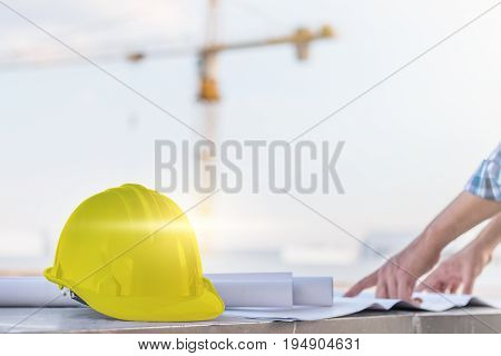 The yellow safety helmet with the man verify blueprint for his project