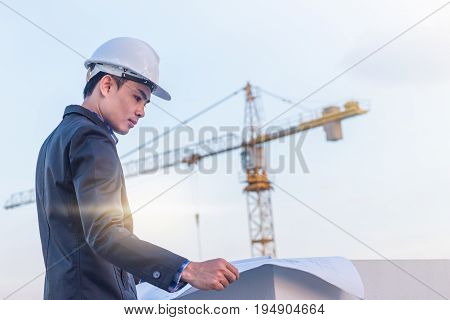 The architect wear white safety helmet and verify the blueprint with commitment on construction site with crane background